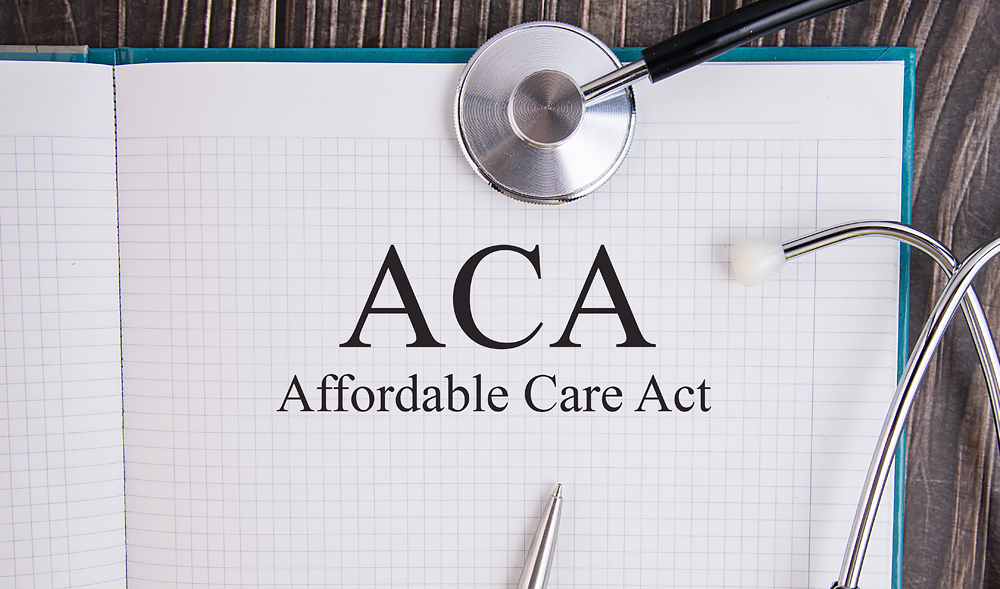 Magnifying glass over Affordable Care Act (ACA) text.